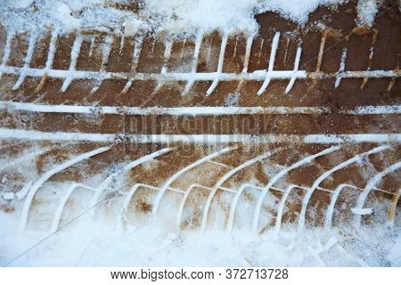 Traces of tire treads in the snow in winter