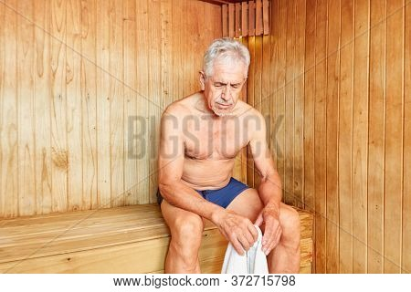 Old man sits exhausted in the sauna and sweats for health at the spa