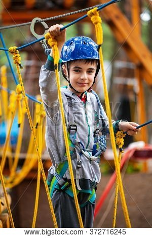 Young Boy Climbing Pass Obstacles In Rope. Child In Forest Adventure Park.