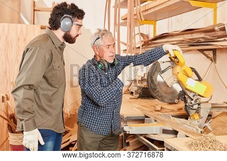 Carpenter master and trainee at the chop saw in the carpentry or joinery