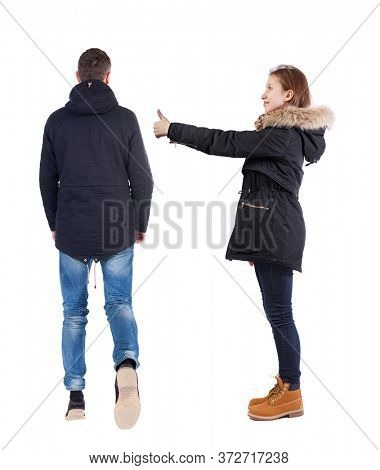 Back view of couple couple in winter jackets showing thumbs up. beautiful friendly girl and guy together. Rear view people collection. backside view of person. Isolated over white background.
