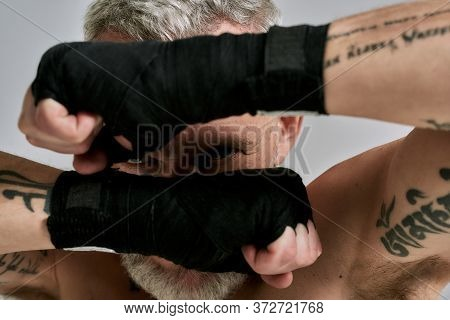 Close Up Of Middle Aged Athletic Man, Kickboxer Hiding His Face Behind Wrapped Hands In Studio Over