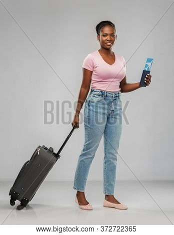 travel, tourism and vacation concept - happy young african american woman with air ticket, passport and carry-on bag over grey background