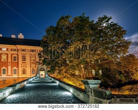 Stone Bridge Leading Towards A Historical Building At Night With The Moon Shining Through A Tree Cro