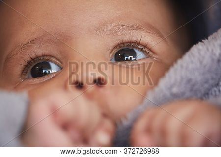 Close Up Portrait Of Cute Mixed-race Baby Sucking Thumb With Focus On Big Hazel Eyes With Long Lashe