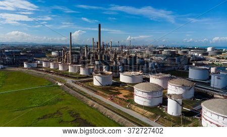 Aerial View Of A Lot Of Oil Depot Gas Storage Tank Around Oil Refinery Tower And Green Grass At Side