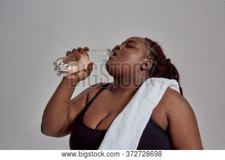 Tired Plump, Plus Size African American Woman In Black Sportswear Drinking Water From The Bottle Aft