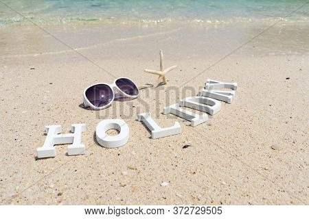 Holiday Alphabet Sunglasses And Starfish On The Sand Beach On Sunny Day With The Beautiful Sea Water