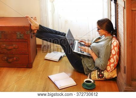 Young Female Freelancer Sitting On Floor Near Cup Of Coffee And Open Planner And Browsing Laptop Whi