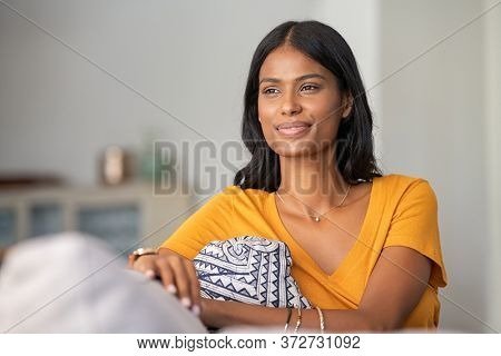 Young indian woman relaxing on couch at home while looking away. Thoughtful smiling mixed race girl daydreaming while sitting on sofa at home. Pensive middle eastern woman thinking.