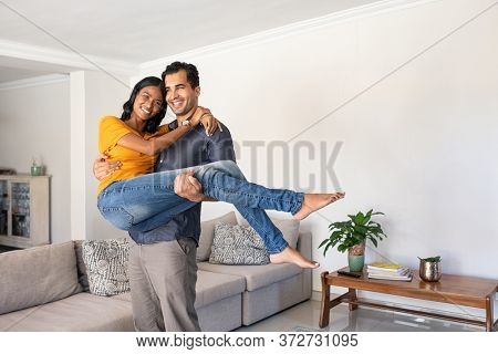 Romantic young middle eastern man lifting woman. Joyful couple moving into their new home with husband carrying his wife. Man carrying indian woman in his arms moving in booking house for vacation.