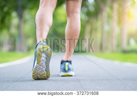 Young Adult Male In Sport Shoes Running In The Park Outdoor, Runner Man Jogging And Walking On The R