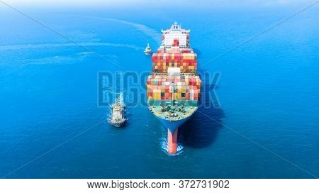 Aerial Of Cargo Ship Carrying Container With Tugboat Working Near And Running For Export  Goods  Fro