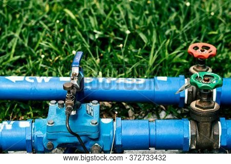Outdoor Water Valve Closing System, The Main Green Grass Floor Consists Of A Brass Plumbing Gate Val