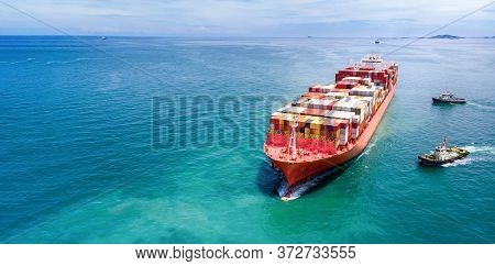 Aerial In Front Of Cargo Ship Carrying Container And Running With Tug Boat For Export  Cargo .