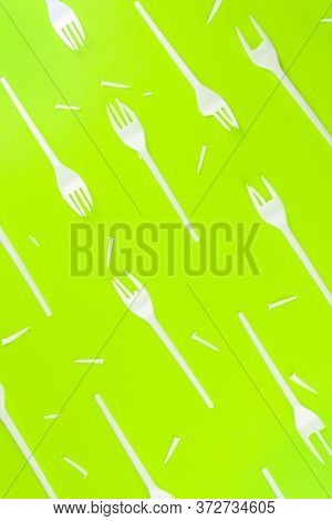 Pattern Of A Lot Of Broken Plastic Forks On A Green Background. The Concept Of Environmental Problem