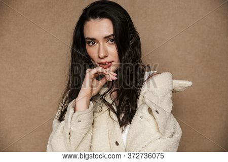 Photo of seductive nice woman in jacket posing and looking at camera isolated over beige background