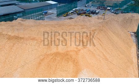 Aerial Top View Of Woodchip With Backhoe Working Loading Chip To Truck Concept Green Fuel For Save E