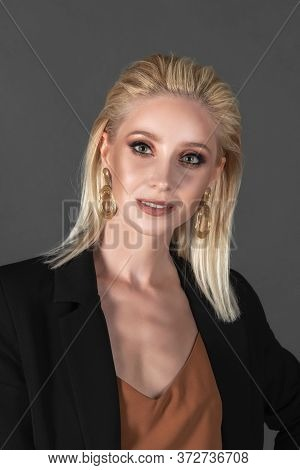 Close-up Portrait Of A Beautiful Girl With Long Blond Hair In An Elegant Black Suit Standing Against