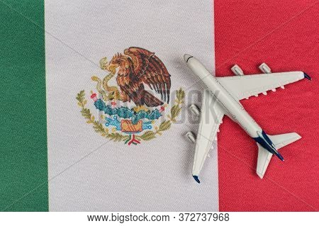 Flag Of Mexico And Model Airplane. Resumption Of Flights After Quarantine. Travel To Mexico.