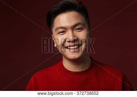 Image of happy young asian man smiling and looking at camera isolated over burgundy background