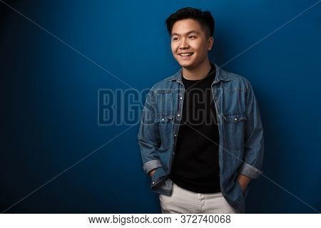 Image of pleased handsome asian man smiling and looking aside isolated over blue background