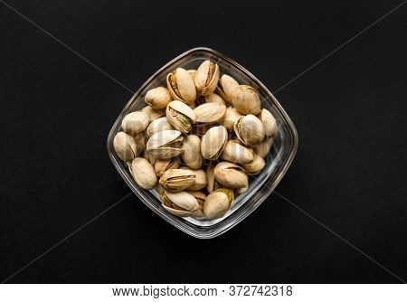 Pistachios In A Small Plate On A Black Table. Pistachio Is A Healthy Vegetarian Protein Nutritious F
