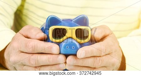 Elderly Man In Yellow Pullover Hugs Blue Piggy Bank With Sunglasses Under Bright Light Extreme Close