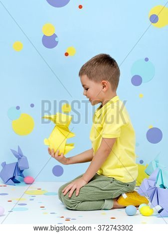Cute Little Boy Playing With Coloured Pastel Easter Origami Bunnies. Kid Holds Yellow Paper Bunny In