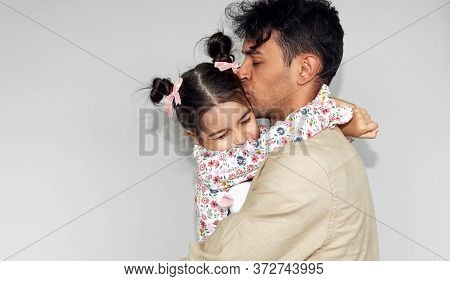 Side View Studio Image Of Father Hugging His Daughter Against The Gray Wall. Happy Child And Daddy F
