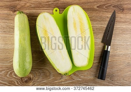 Whole Squash Marrow, Halves Of Squash Marrow On Green Plastic Cutting Board, Kitchen Knife On Wooden