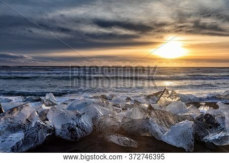 Sunrise on Diamond Beach, Iceland. The black volcanic sands are littered with chucks of glacial ice that have broken from the nearby Jökulsárlón glacier lagoon and drifted out towards the sea.