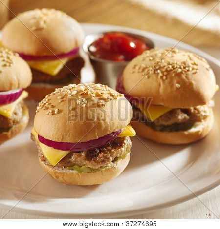mini burgers with cheese, onion and pickle closeup with ketchup