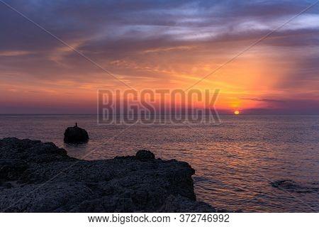 Beautiful Orange Sunset Over The Sea. The Sun Sets On The Horizon. Relaxing Sea Landscape. Purple Sh