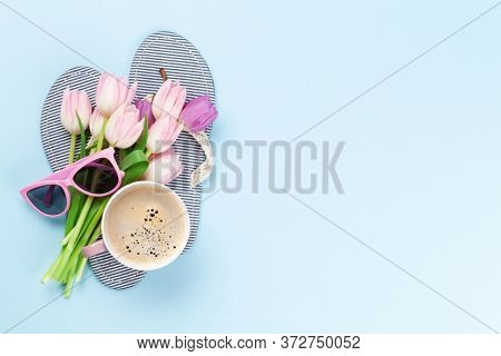 Beach flip flops with flowers, coffee and sunglasses on blue background. Summer vacation concept. Flat lay with copy space