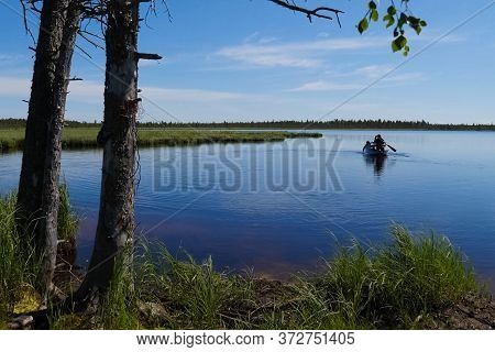 Fishermen On The Boat Approach To The Shore. Fishermen In Ugra.