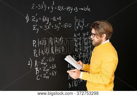 Bearded teacher in casualwear rewriting formulas on blackboard from his copybook before giving task to his online audience