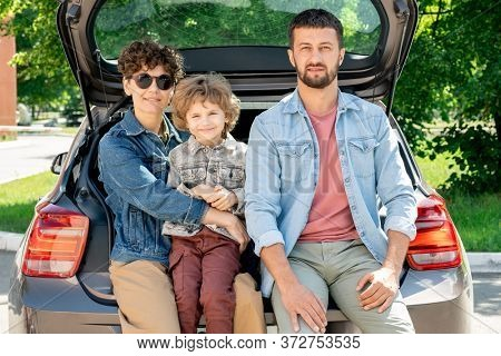 Happy young affectionate family of father, mother and son of elementary age sitting in the car trunk in front of camera on sunny summer day