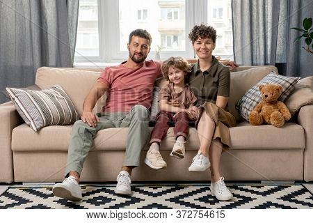 Happy young man, his pretty wife and their cute little son in casualwear looking at you while sitting on couch in living-room against window