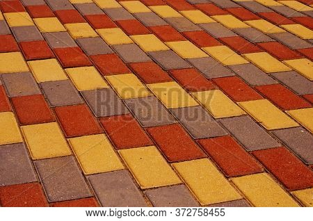 Sidewalk With Gray, Yellow And Red Cement Rectangular Tiles.