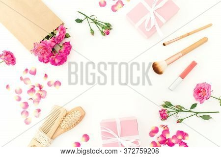 Beauty Frame Of Pink Roses With Hairbrush, Tassel And Gifts On White Background. Flat Lay, Top View
