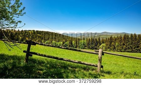 Wooden Fence On A Mountain Pasture In Beautiful Green Forested Hilly Landscape, Krkonose Mountains,