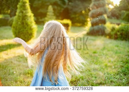 Child Whirling, Dancing Plays On The Meadow. Girl Having Fun With Bubbles. Cute Little Longhair Blon