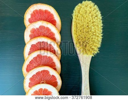 Grapefruit Cut Into Circles, Natural Wooden Brush For Dry Massage Against Cellulite On A Black Backg