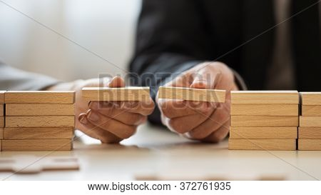 Closeup View Of Businessman And Businesswoman Making A Bridge Of Wooden Blocks Between Two Stacks Of