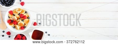 Pancake Cereal With Berries On A White Wood Banner Background. Mini Pancakes In A Bowl, Corner Borde