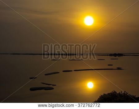 Dead Sea. The foggy sun is reflected in the smooth surface of the water. Evaporated salt protrudes above water. The concept of active, environmental and photo tourism