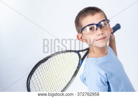 Young squash player with protective glasses and squash racket