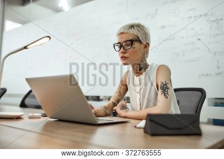 Young And Beautiful Tattooed Woman With Short Haircut Using Laptop While Sitting At Her Working Plac