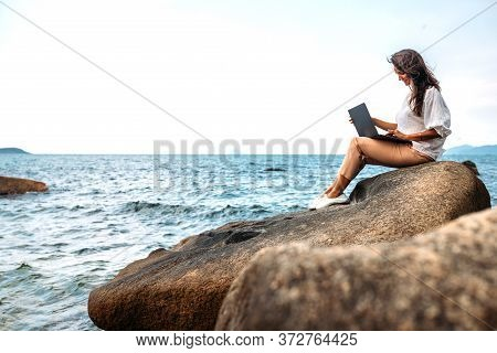 Young Successful, Smiling Girl Working Using A Laptop, Sitting On A Rocky Seashore. Business Woman W